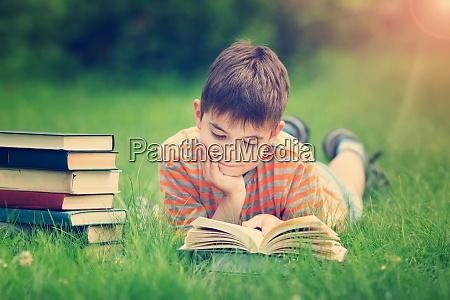 siebenjaehriges kind liest ein buch auf