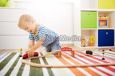 kleines kind spielt mit der eisenbahn