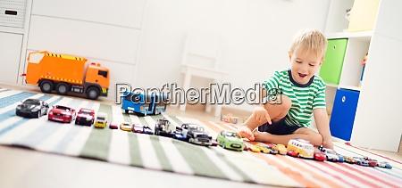 kleines kind spielt mit spielzeugautos
