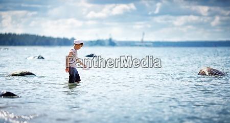 achtjaehriger junge spielt am strand in
