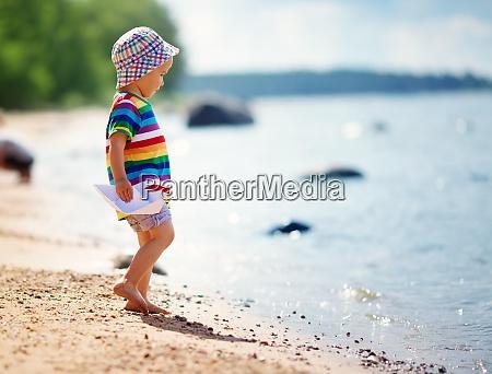 kleiner junge spielt am strand im