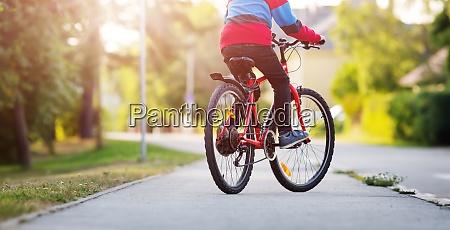 kind auf dem fahrrad auf asphaltstrasse
