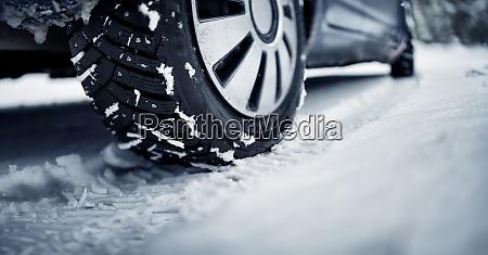 nahaufnahme des autoreifens auf winterbedeckter strasse