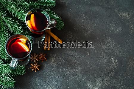 weihnachtsgluehwein mit gewuerzen auf dunklem betonhintergrund