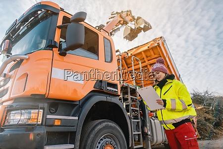 arbeiter beobachtet einen lastwagen mit greifer