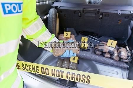 polizist haelt drogenpaket im kofferraum eines