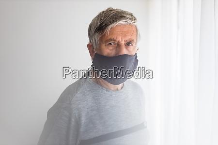 senior mann traegt eine gesichtsmaske waehrend