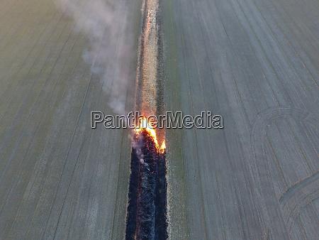 brennendes gras entlang des bewaesserungskanals rauch