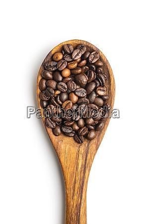 geroestete kaffeebohnen auf holzloeffel