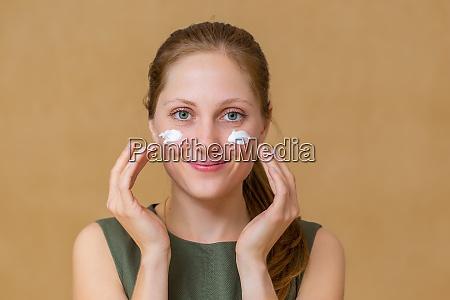 schoene junge frau die gesichtskosmetik mit