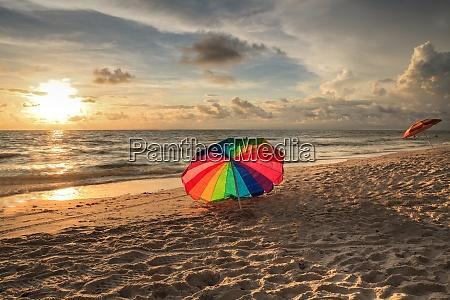 regenbogenschirm auf weissem sand im delnor
