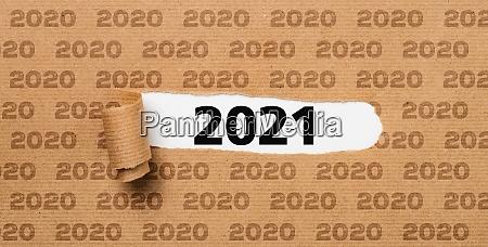 zerrissenes papier enthuellt die zahl 2021