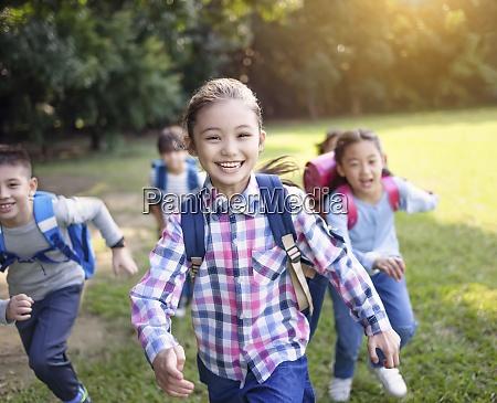 gruppe von grundschulkindern laeuft auf dem