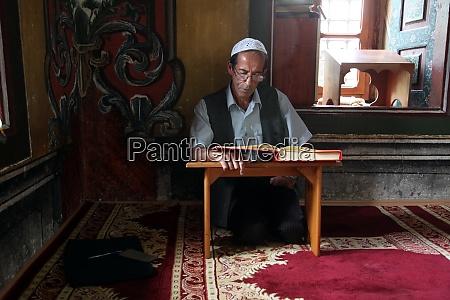 muslimischer mann liest den koran in