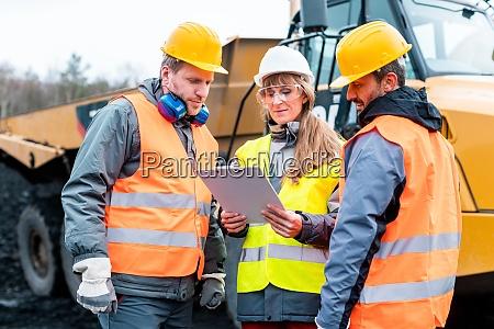 drei arbeiter in einem steinbruch diskutieren