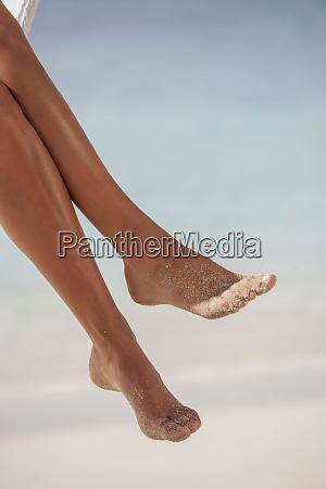 frauenbeine am tropischen strand
