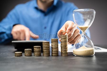 erhoehung geld coin stack konzept sanduhr