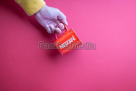 hand haelt nescafe becher auf rotem