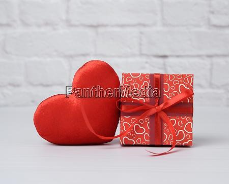 roter karton mit geschenk und plueschherz
