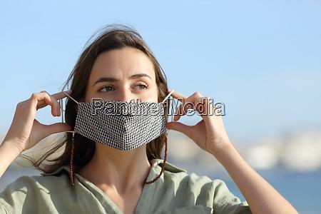 glueckliche frau ausziehen maske wegen covid