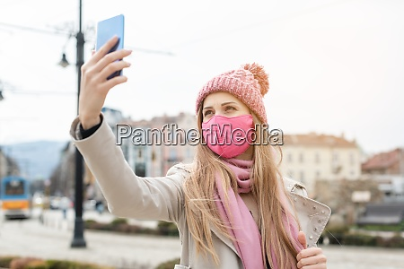 frau traegt corona maske machen selfie