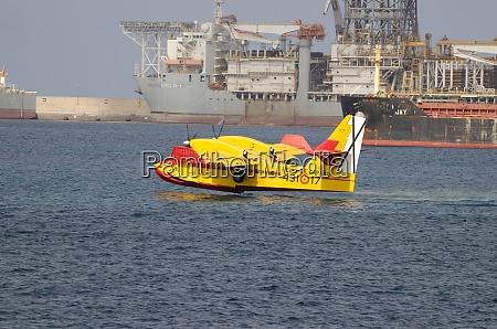 loeschflugzeug sammelt meerwasser um einen waldbrand