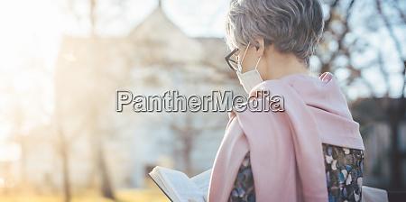seniorin mit gesichtsmaske liest die bibel