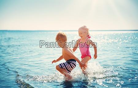 junge und maedchen spielen am strand