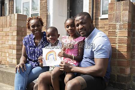 portraet glueckliche familie mit regenbogen zeichnung