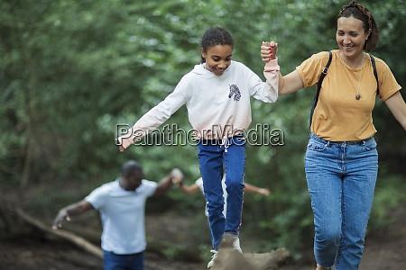 mutter hilft tochter entlang gefallenen baumstamm