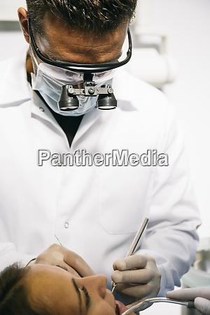 maennlicher zahnarzt in chirurgischen lupen und