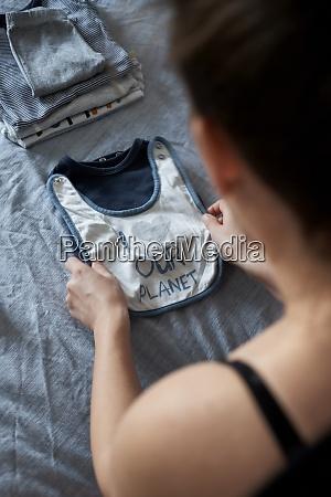 schwangere frau falten baby kleidung auf