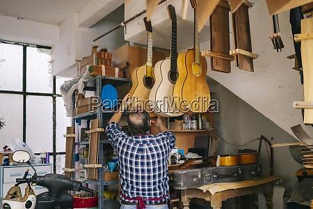 senior mann haengen gitarre in einer