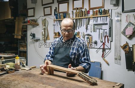luthier macht griffbrett der gitarre waehrend