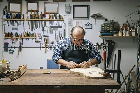handwerker der gitarre in der werkstatt