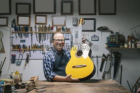 laechelnder mann haelt gitarre waehrend er