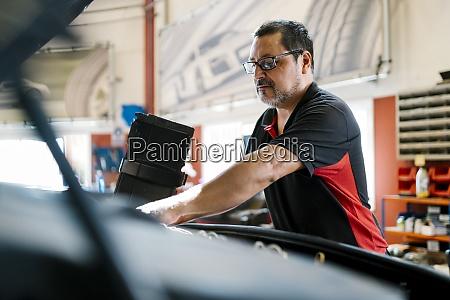 maennlicher mechaniker repariert auto waehrend in
