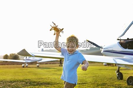 netter kleiner junge spielt mit spielzeugflugzeug