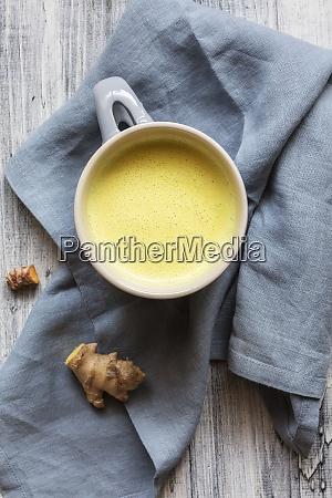 goldene milch mit wurzel auf serviette