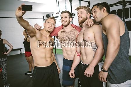 vier athleten im fitnessstudio machen selfie