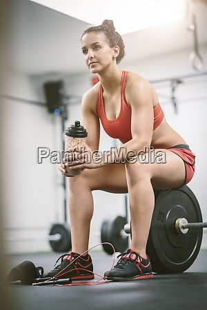 frau im fitnessstudio macht eine pause