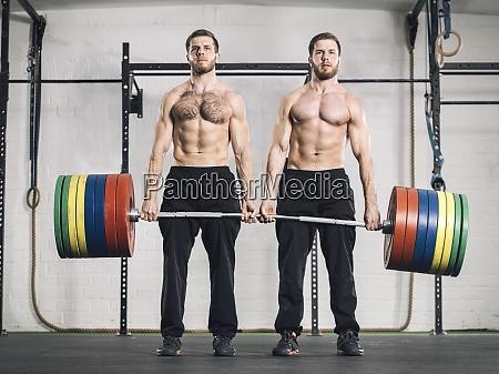zwillingsbrueder gewichtheben in fitness studio