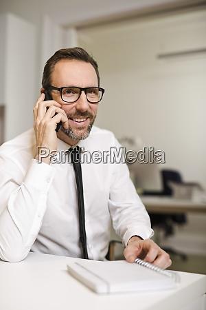 geschaeftsmann am telefon am schreibtisch im