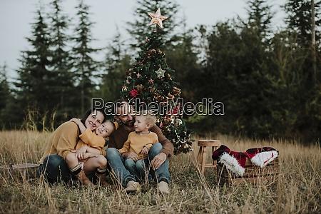 laechelnde familie sitzt am weihnachtsbaum auf