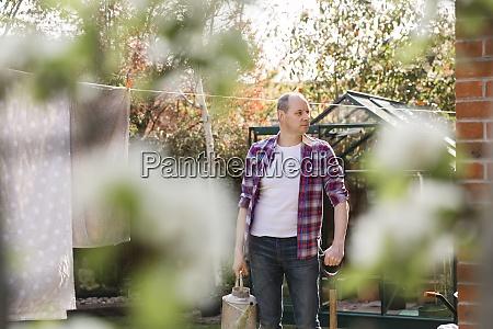 mann mit giesskanne im garten