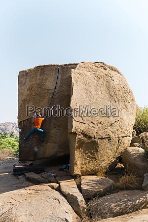 maennlicher kletterer steigt auf riesigen felsbrocken