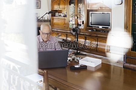 AElterer mann mit laptop am tisch