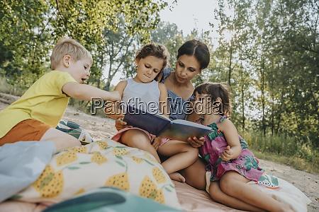 reife frau und drei kinder lesen