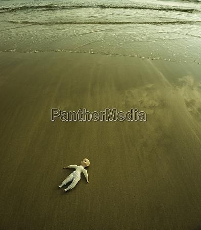 puppe liegt am nassen sandstrand am
