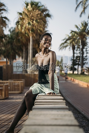 smiling, woman, looking, away, while, sitting - 29122964